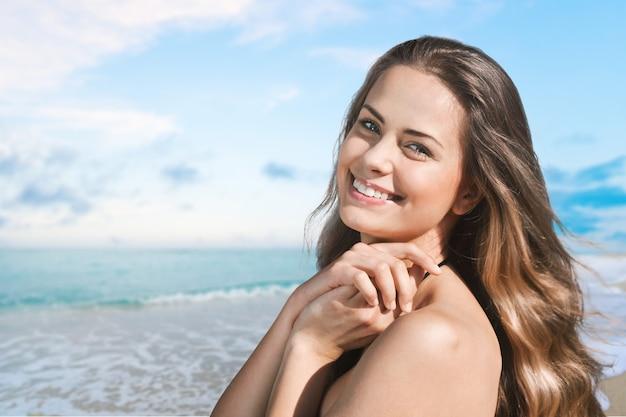 海の背景上の美しい女性。日焼け。スキンケアと保護。休暇