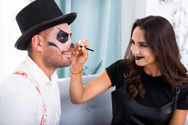 Beautiful woman painting husbands face for halloween