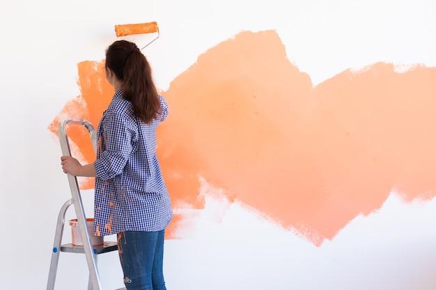 그녀의 새 아파트에서 아름 다운 여자 그림 벽입니다. 혁신 및 재 장식 개념. 공간을 복사하십시오.