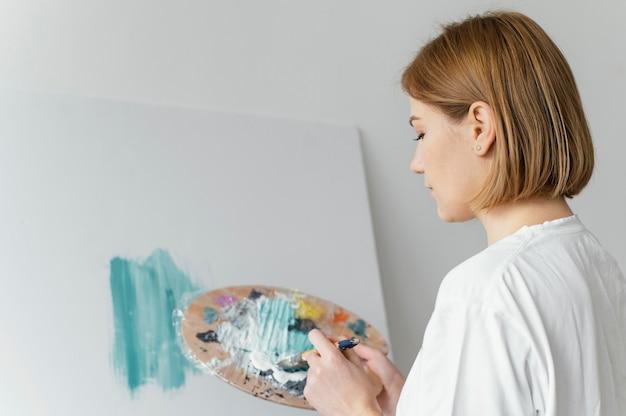 Bella donna che dipinge con acrilici su tela