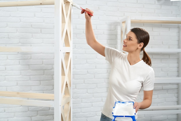 Beautiful woman painting wooden rack in white color