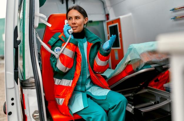 Фельдшер красивой женщины в униформе отвечает на телефонный звонок, сидя в современной машине скорой помощи.