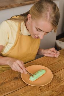 美しい女性のパティシエがエクレアを飾ります。製菓または料理コースのコンセプト