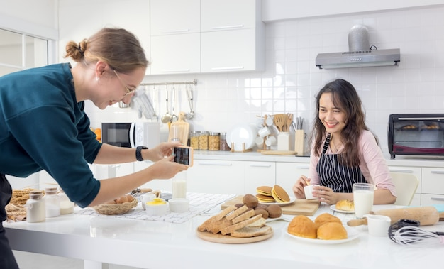 別の女性がそうしている彼女のスナップショットを撮るとき、美しい女性のパティシエが調理台でパン生地をこねています。