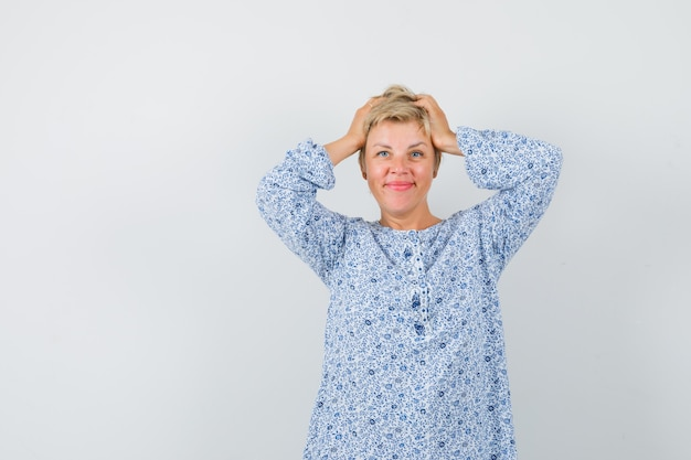 Beautiful woman in patterned blouse clasping head with hands and looking cute , front view.