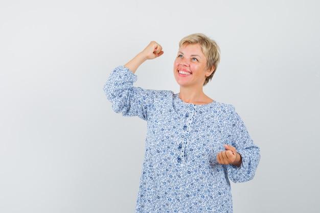 Bella donna in camicetta fantasia che mostra la forza del suo braccio e sembra felice, vista frontale.