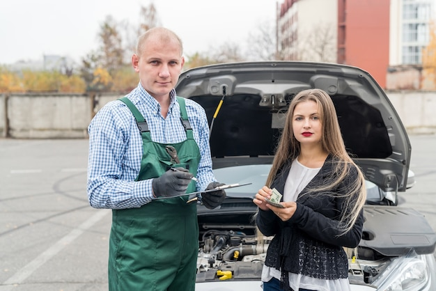 Beautiful woman paying for car service to worker