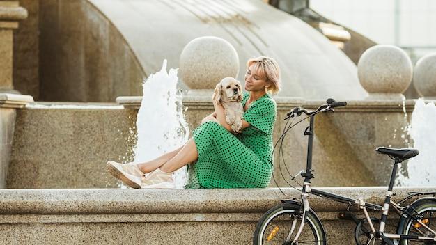 彼女のかわいい犬をかわいがる美しい女性