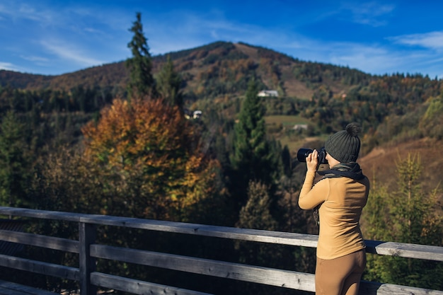 Beautiful woman photographs nature on the mountain in autumn.