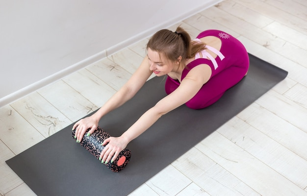 Beautiful woman pilates instructor stretching and warming up using foam roller, working out, wearing pink sportswear, close up. sport and healthy active lifestyle concept.