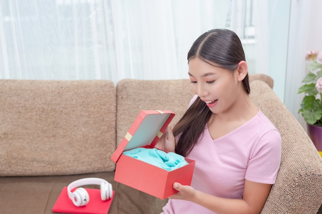Beautiful woman in pink dress, sitting on the sofa, opening a gift box.