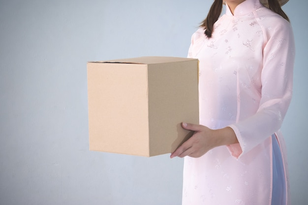Beautiful woman in pink dress and vietnam hat holding box