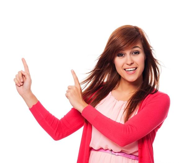 Bella donna in rosa che punta allo spazio della copia