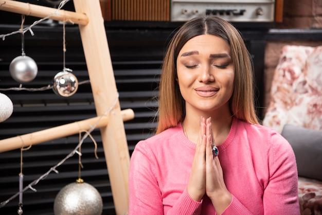 Bella donna in maglione rosa che fa meditazione.