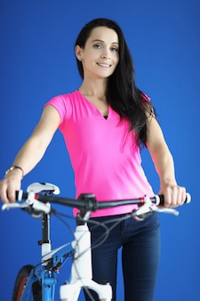 Beautiful woman in pink t-shirt smile and hold bike behind wheel.