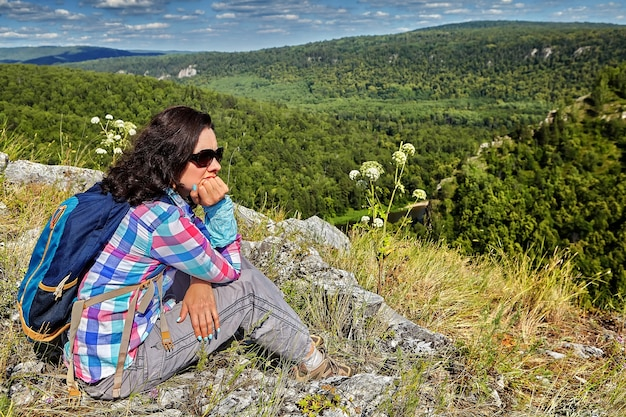 Beautiful woman in  plaid shirt and sunglasses is resting on  top of  mountain on sunny summer day.