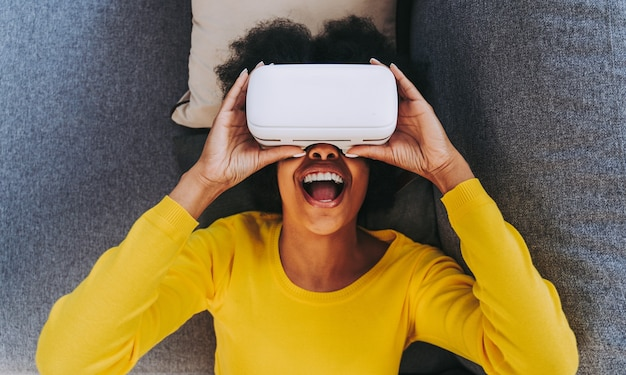 Vrヘッドセットで自宅で遊ぶ美しい女性-拡張現実技術と対話しながらソファに横になっている黒人女性