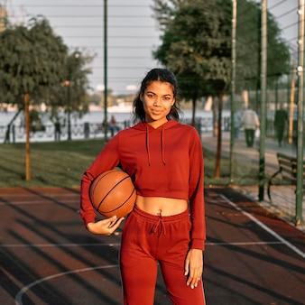 Красивая женщина играет в баскетбол на открытом воздухе