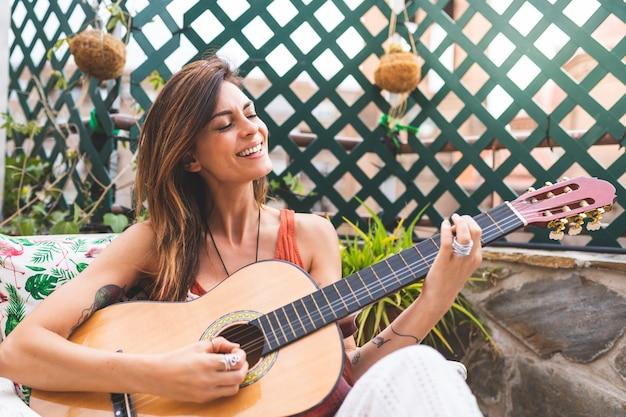 美しい女性が屋外でギターを弾きます。