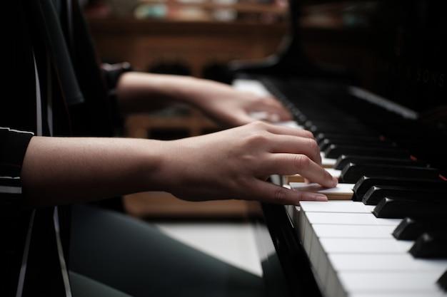 Beautiful woman playing piano, learn to play piano.
