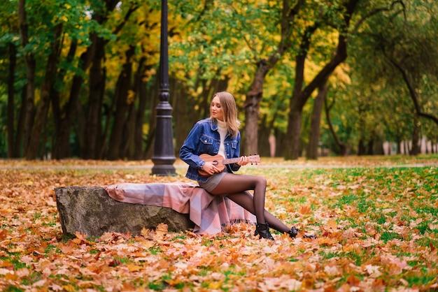 가을 숲에서 야외에서 우쿨렐레 기타를 연주하는 아름 다운 여자