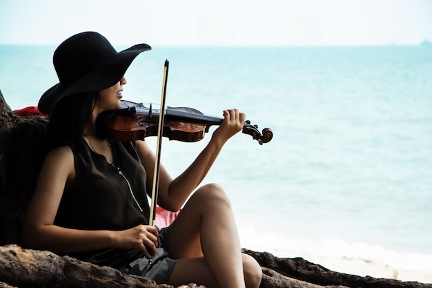 The beautiful woman playing violin on the beach