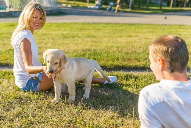子犬のラブラドールと遊ぶ美しい女性