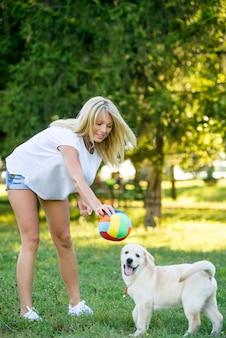 Красивая женщина играет с щенком лабрадором