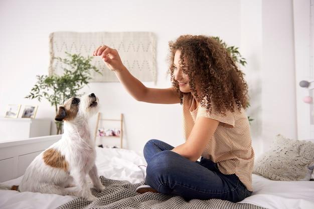 Bella donna che gioca con il cane sul letto