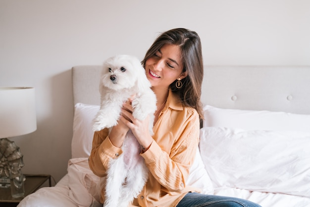 Beautiful woman playing with her cute dog at home