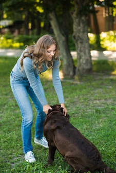 Beautiful woman playing with her dog in park