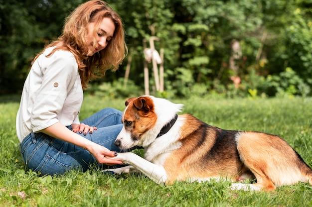 公園で彼女の犬と遊ぶ美しい女性