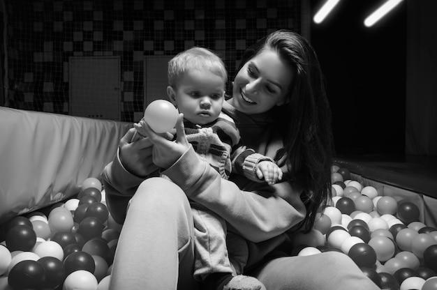 아름 다운 여자는 마른 수영장에서 여자 아기와 함께 재생합니다. 휴일 개념입니다. 엔터테인먼트 몰. 어린이 교육 센터. 혼합 매체