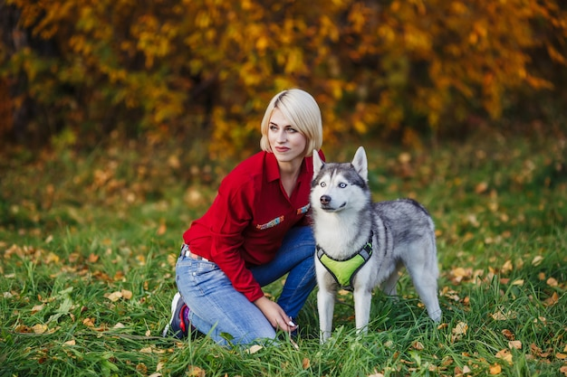 Beautiful woman plays with husky dog in autumn forest