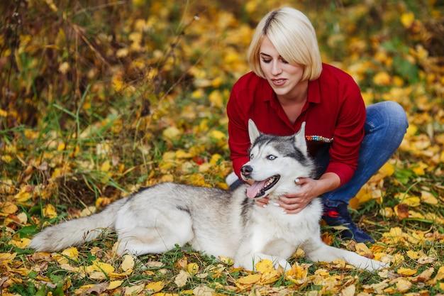 秋の森でハスキー犬と遊ぶ美しい女性