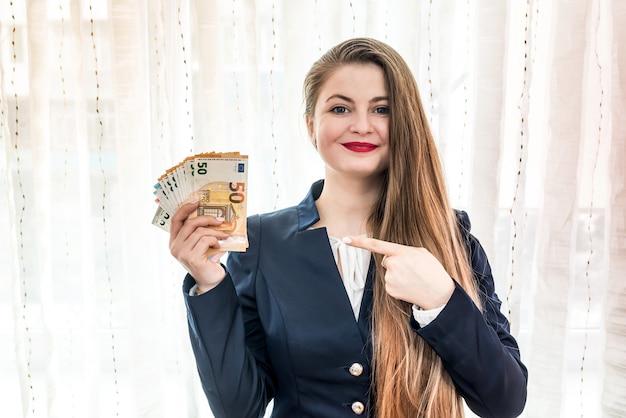 유로 지폐를 손에 가리키는 아름 다운 여자