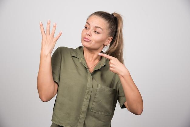 Красивая женщина, указывая на ее руку на серой стене