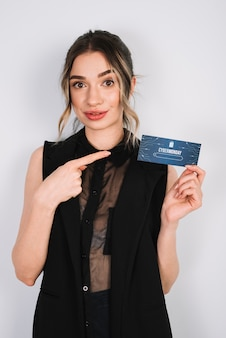 Beautiful woman pointing at card with cyber monday
