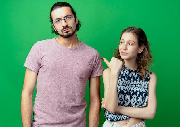Bella donna che punta al suo uomo dispiaciuto e accigliato, giovane coppia uomo e donna oltre il muro verde
