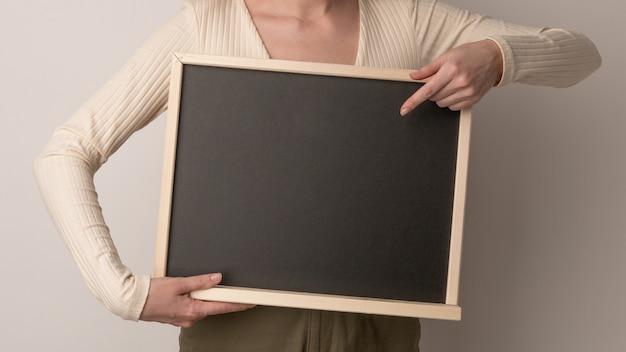 빈 분필 칠판에 가리키는 아름 다운 여자