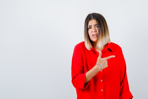 Beautiful woman pointing right in red blouse and looking puzzled. front view.