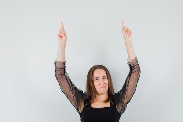 Bella donna rivolta verso l'alto in camicetta nera e guardando dispiaciuto