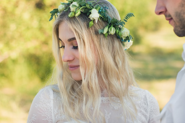夏に花の花輪と自由奔放に生きるスタイルの白いドレスの美しい女性の肖像画