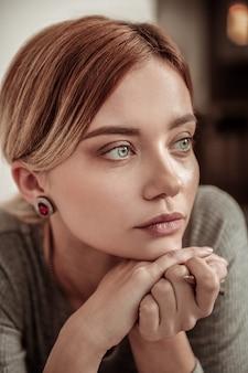 きれいな女性。スタイリッシュな宝石と灰色のドレスを身に着けている美しい若い青い目の女性の肖像画
