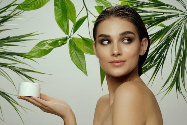 Beautiful woman portrait in palm bushes, beautiful skin of the face