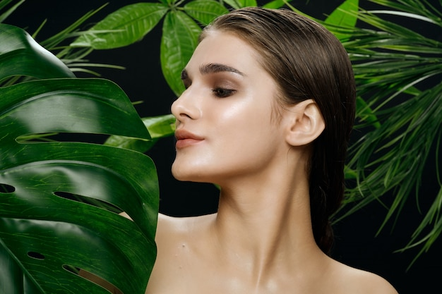 Beautiful woman portrait in palm bushes, beautiful skin of the face