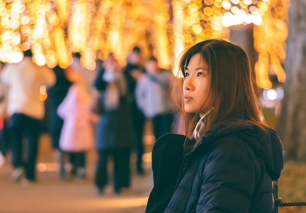 Beautiful woman portrait in winter clothing with christmas light