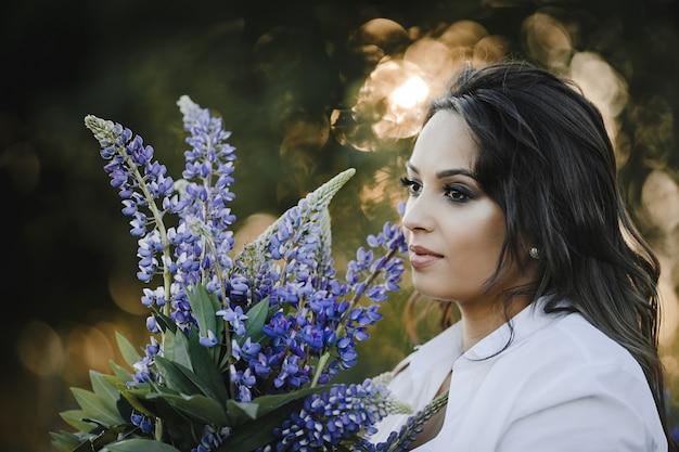 Beautiful woman portrait with bouquet of lupinus, close up