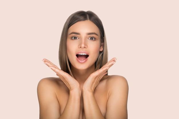 健康な肌と新鮮な毎日のメイクアップの美しい女性の肖像画。色の背景。ピンク