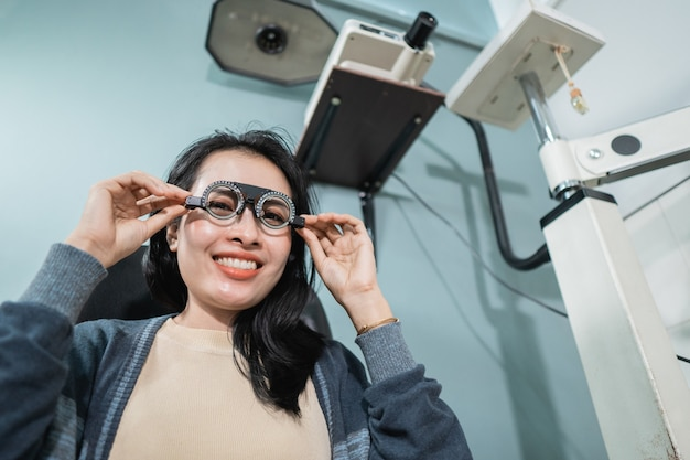 A beautiful woman poses holding measuring glasses that are being used in a room at an eye clinic